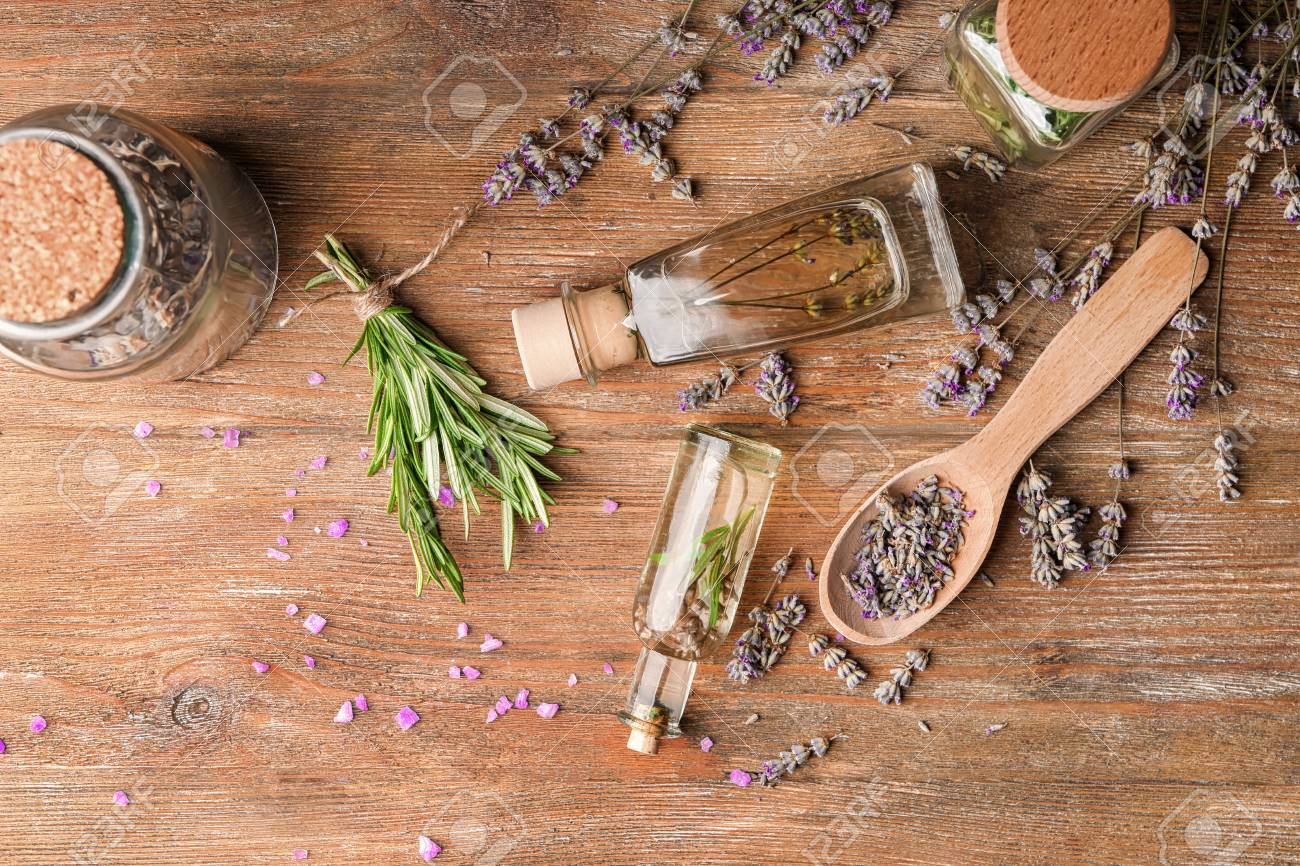 Bottles of essential oil with lavender and rosemary on wooden table - 114675925