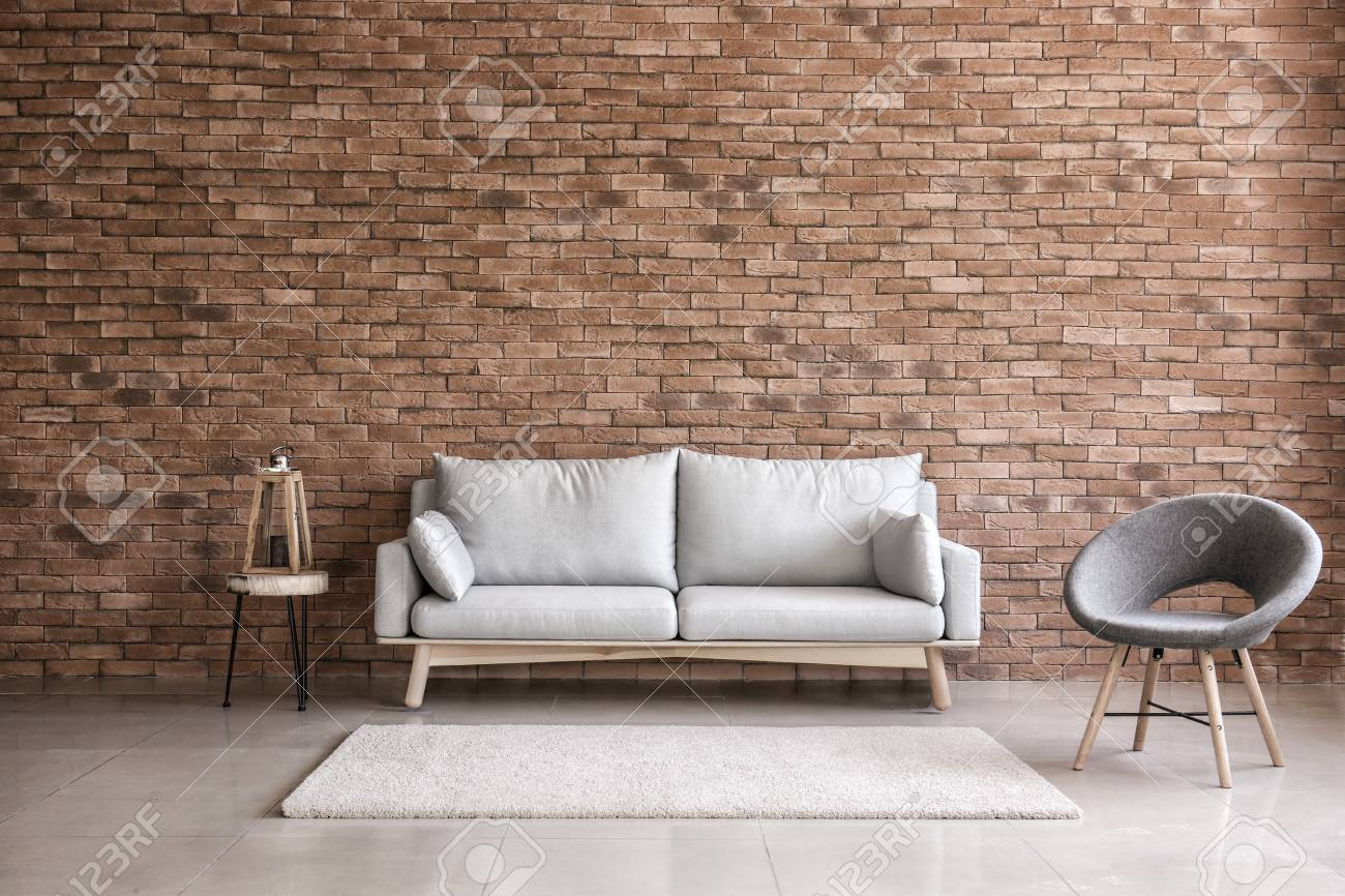 Modern interior of living room with comfortable sofa and armchair near brick wall - 113861359
