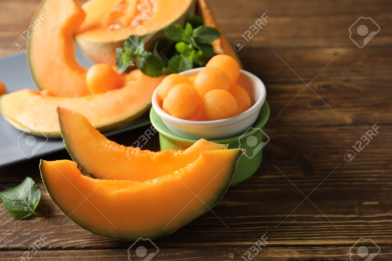 Cut ripe melon and balls on wooden table - 116089526