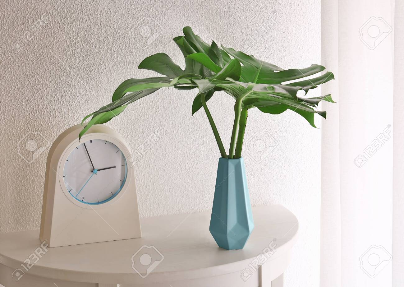 Tropical leaves in vase with clock on table near light wall indoors - 118456187