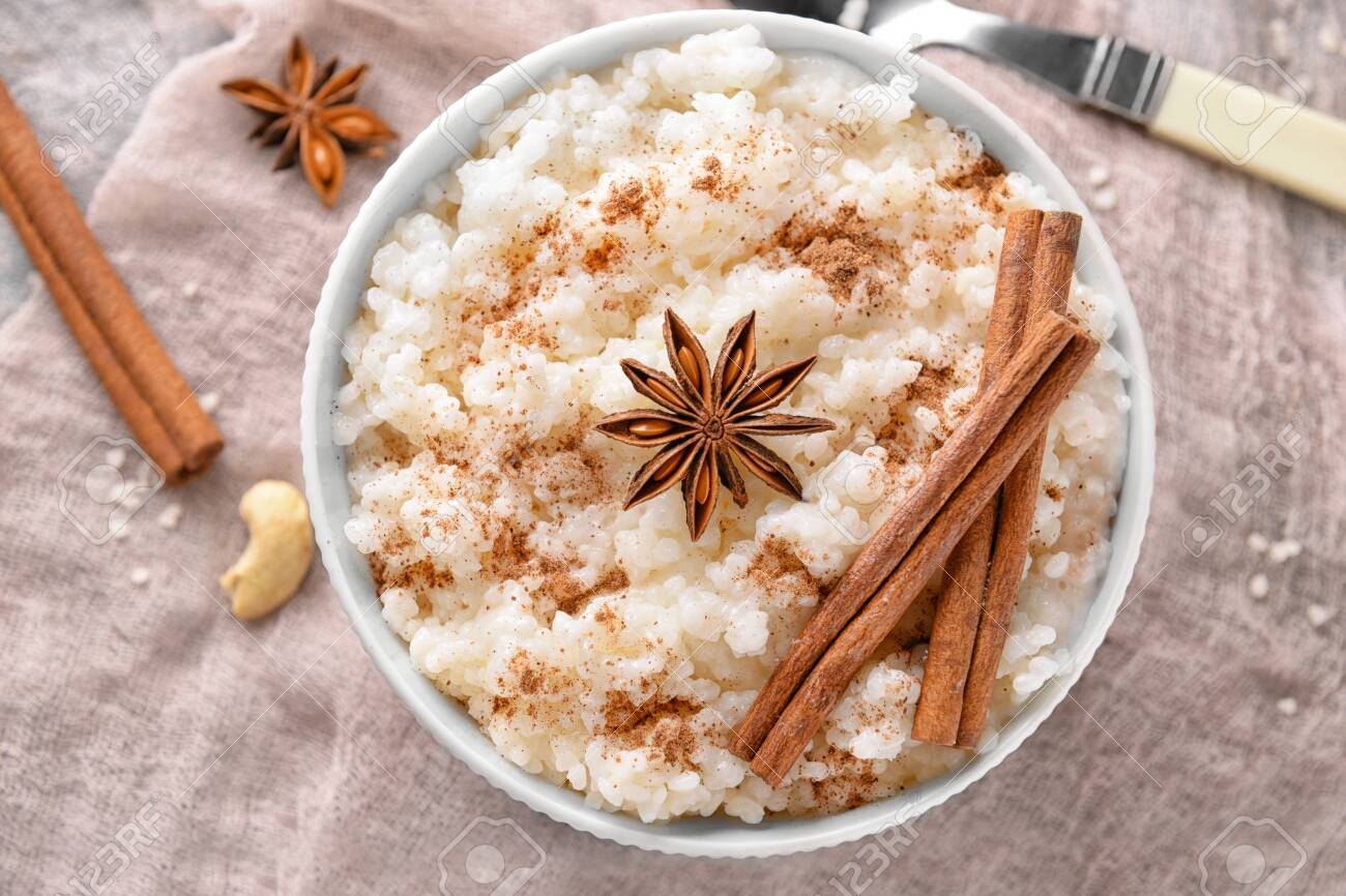 Bowl with tasty rice pudding, cinnamon and anise on gauze cloth - 115051098