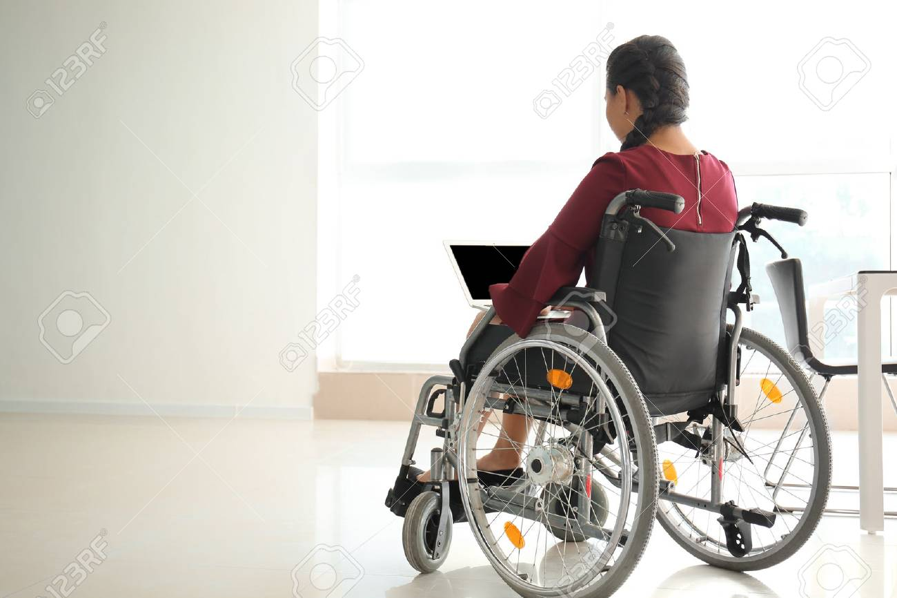 Asian woman in wheelchair working with laptop in office - 115053280
