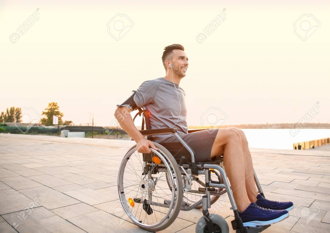 Young man in wheelchair listening to music outdoors - 119746590
