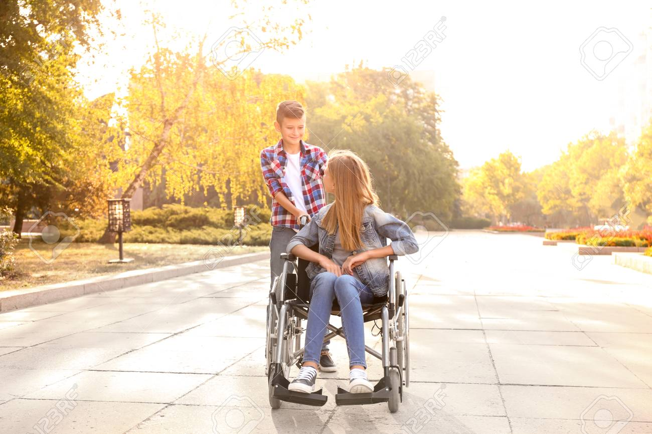Teenage girl in wheelchair and her brother outdoors - 119754077