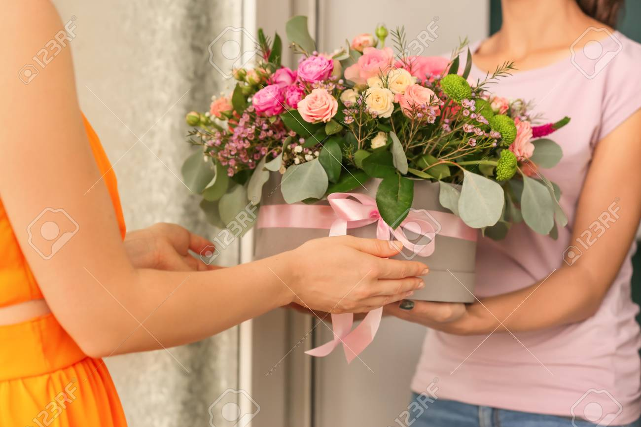Young woman receiving gift box with beautiful flowers from courier - 115142045