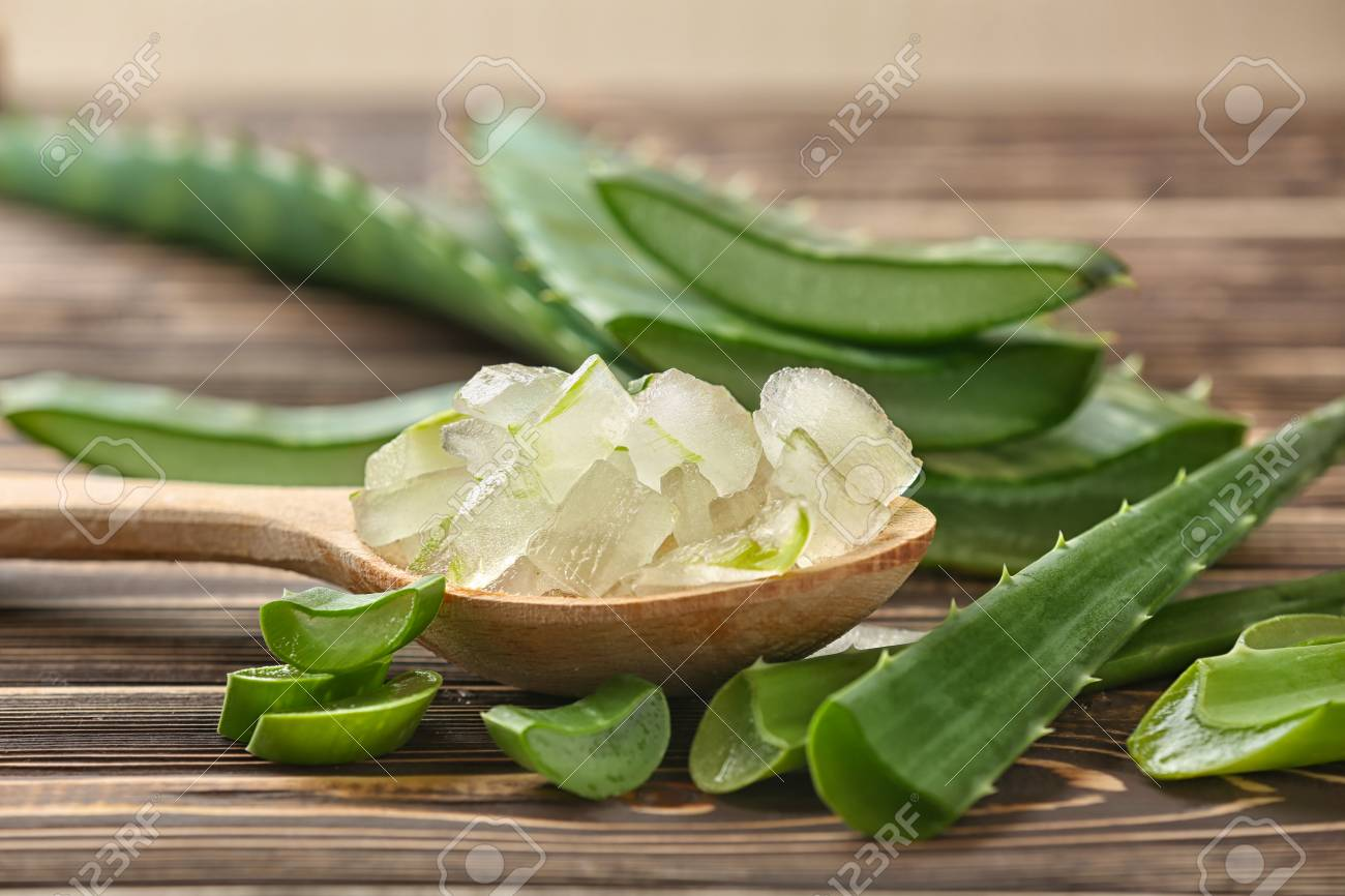 Spoon with aloe vera on wooden table - 115228837