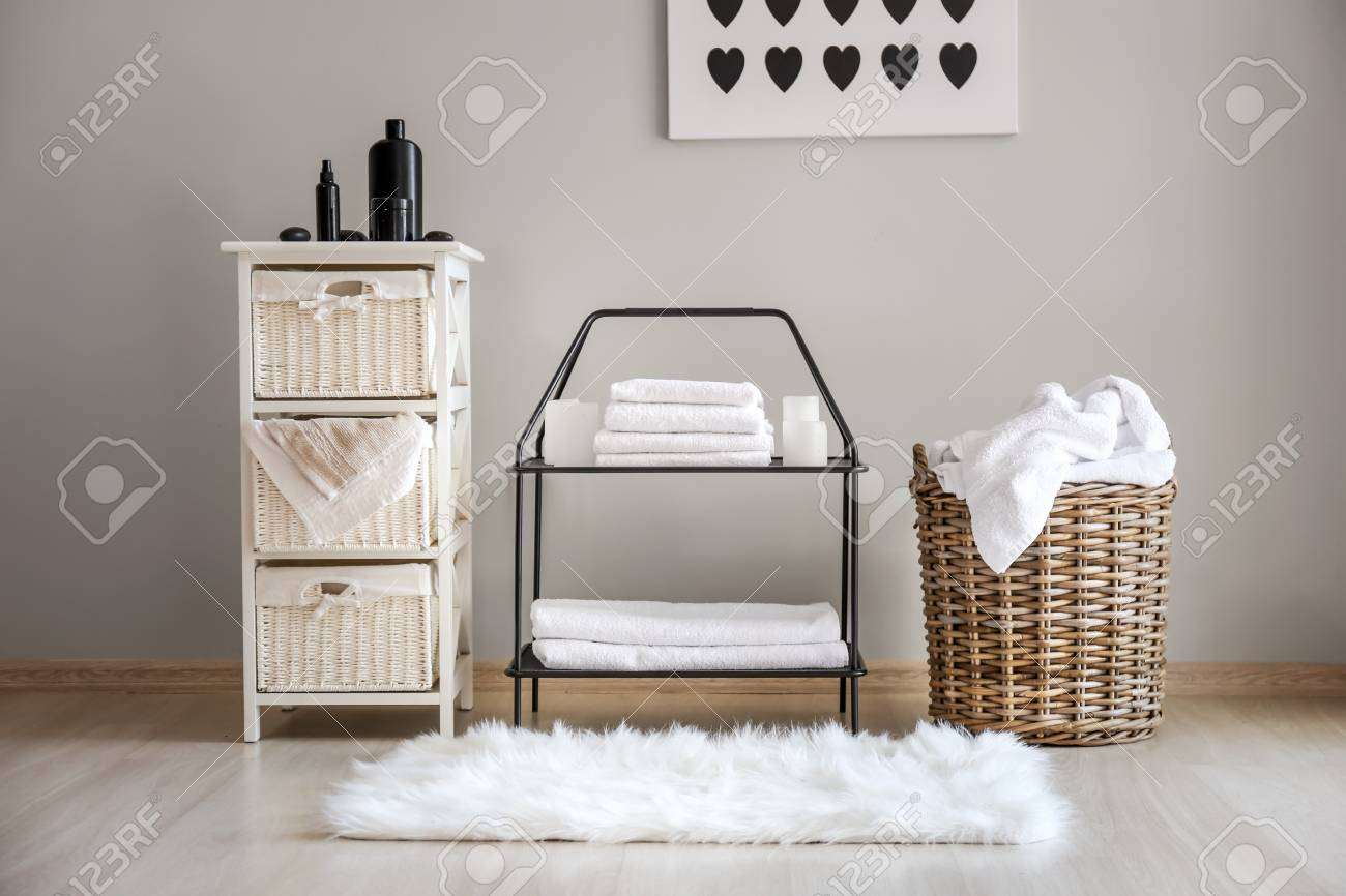Wicker baskets with dirty laundry and folded clean towels on shelves - 115238828