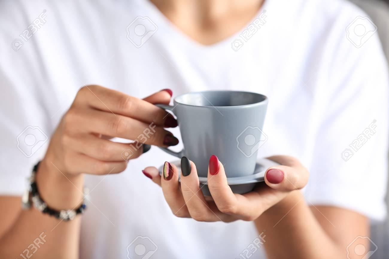 Woman with stylish beautiful manicure drinking coffee, closeup - 116095686