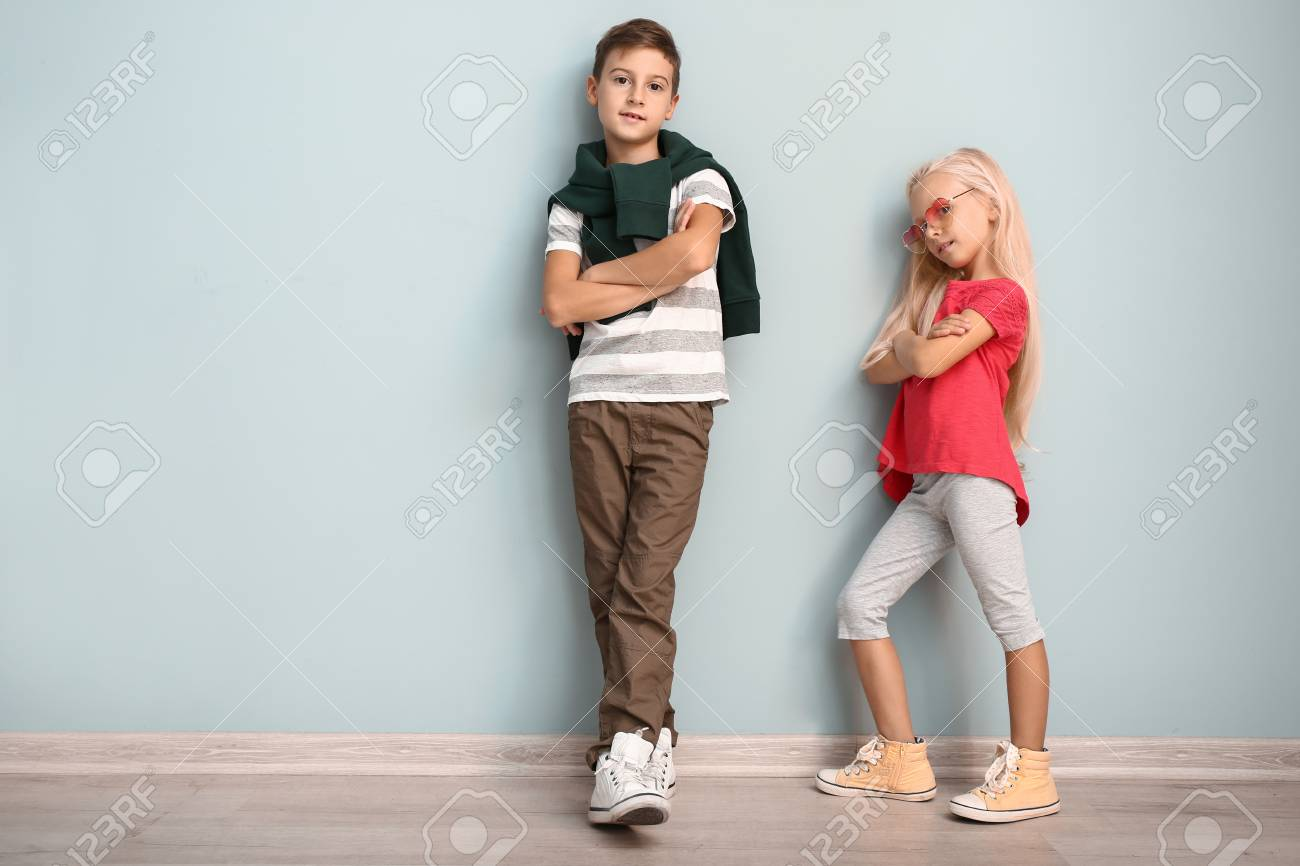 Cute boy and girl in fashionable clothes near color wall - 115307666