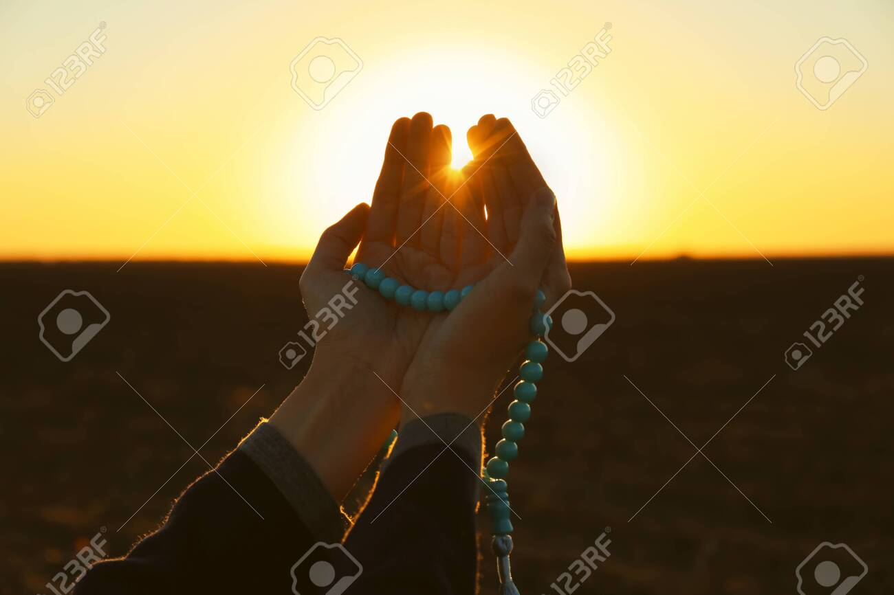 Young Muslim woman praying with beads outdoors at sunrise - 115326198