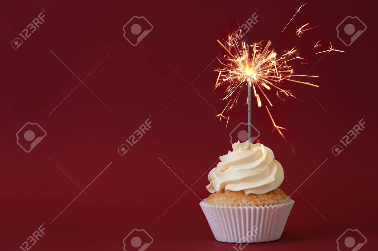 Delicious cupcake with sparkler on color background - 115543942