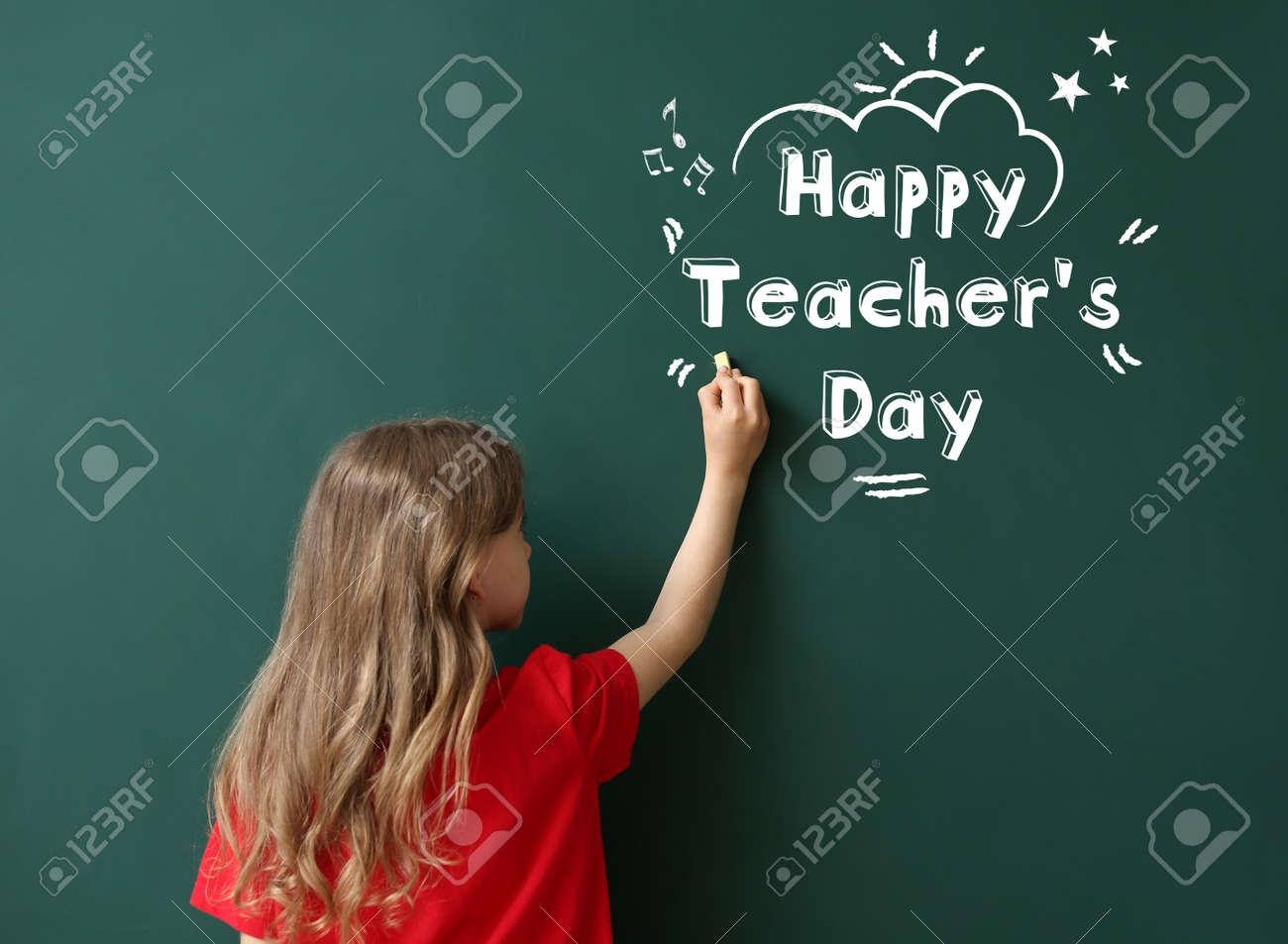 Cute little schoolgirl writing text HAPPY TEACHER'S DAY on blackboard in classroom - 166076604