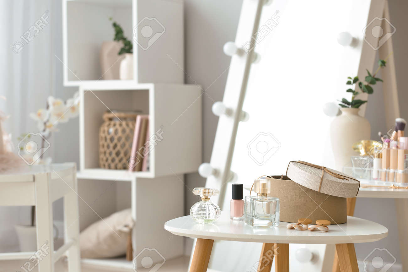 Table with accessories and cosmetics in modern makeup room - 164481402