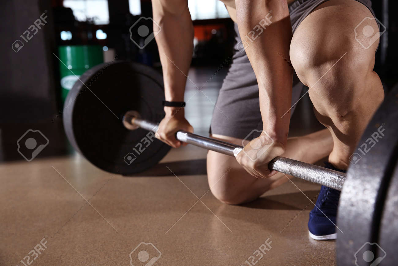 Sporty young man training with barbell in gym - 165000506