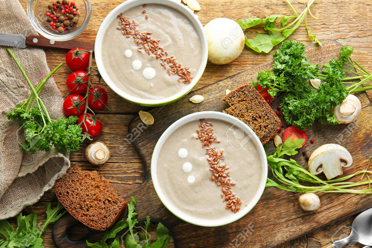 Composition with tasty mushroom cream soup on wooden table - 165156279