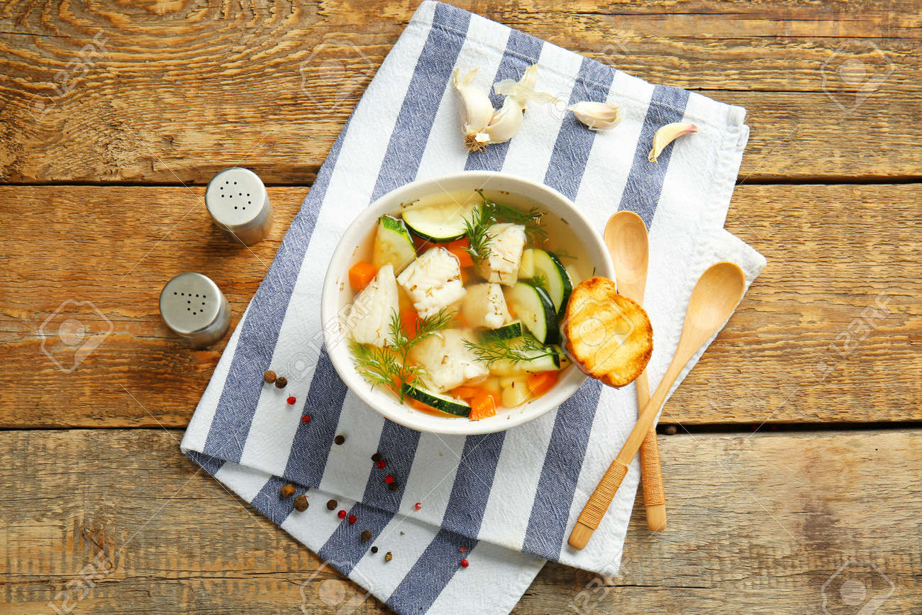 Bowl of tasty soup on wooden table - 165114789