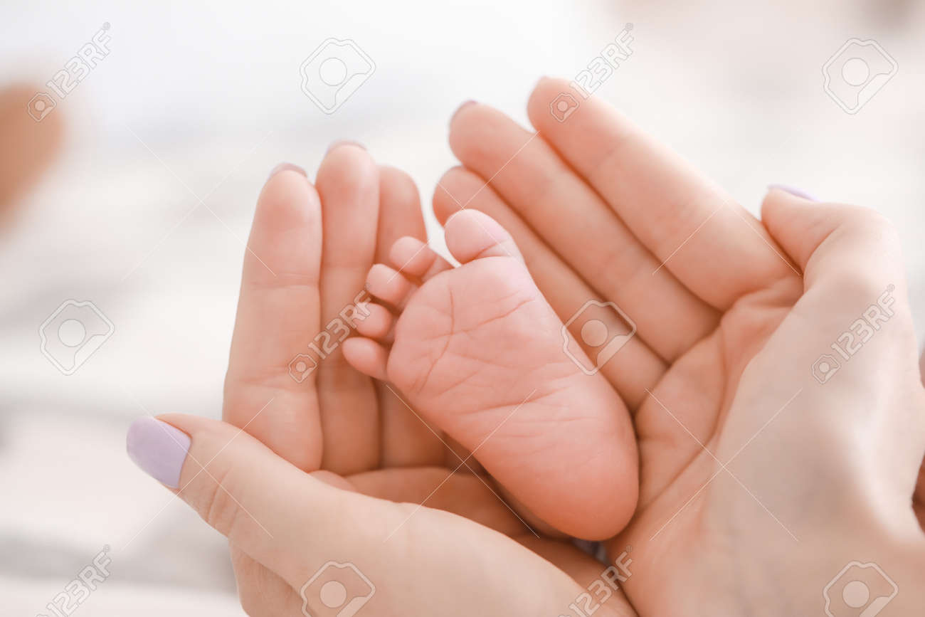 Mother's hands with tiny baby leg, closeup - 165413660