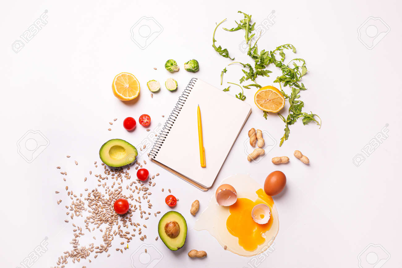 Notebook with healthy products on white background. Diet concept - 165514602