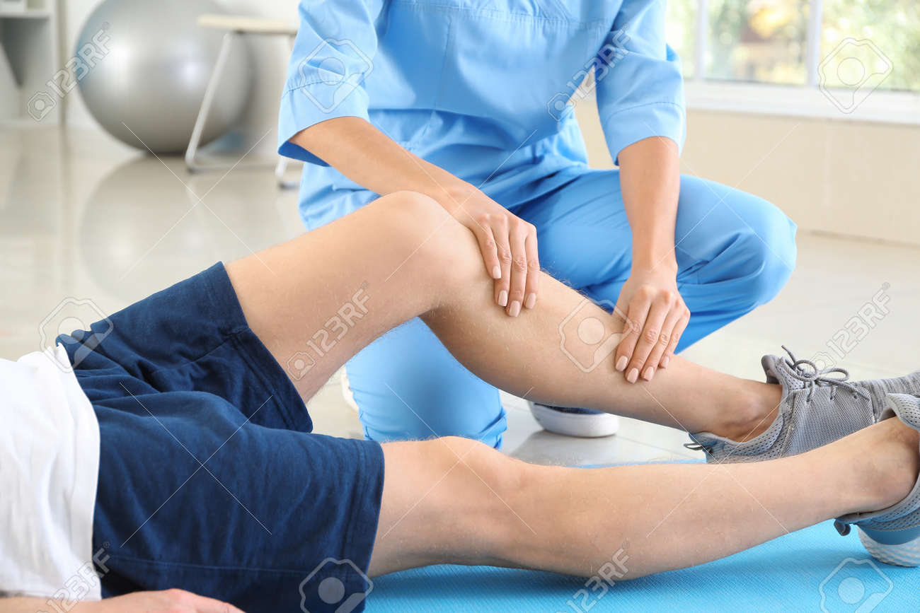 Physiotherapist working with male patient in rehabilitation center - 165904580