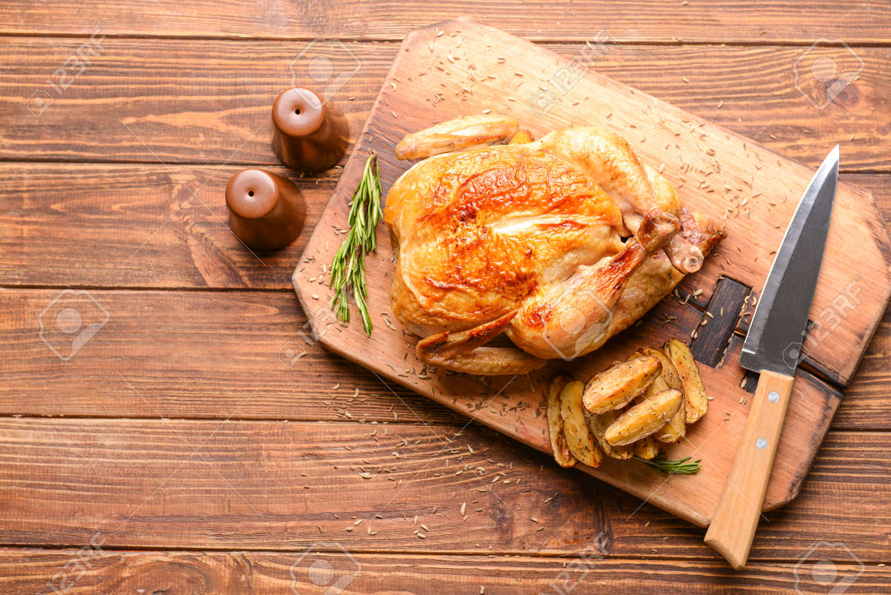 Board with baked chicken and potato on wooden table - 165734271