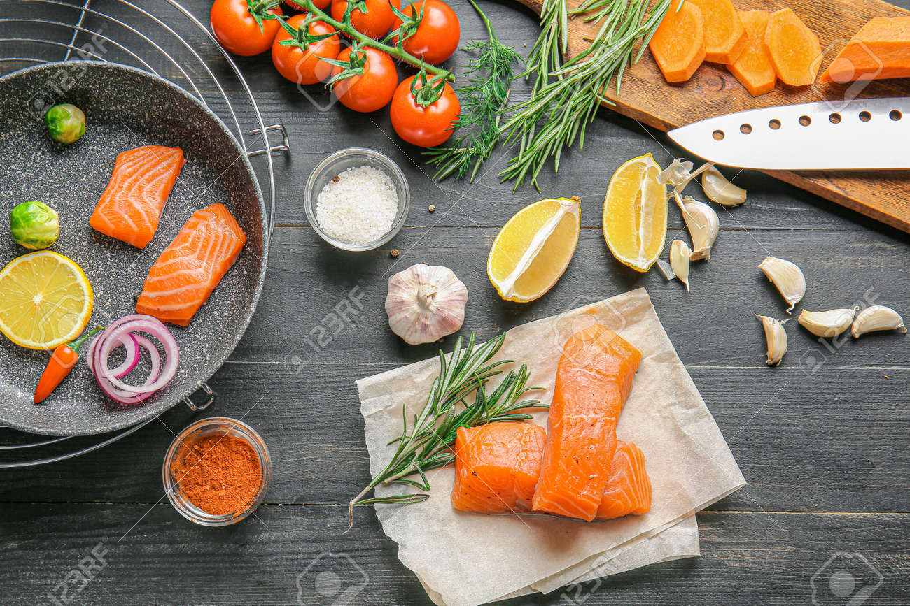 Composition with fresh raw salmon on table - 165917394