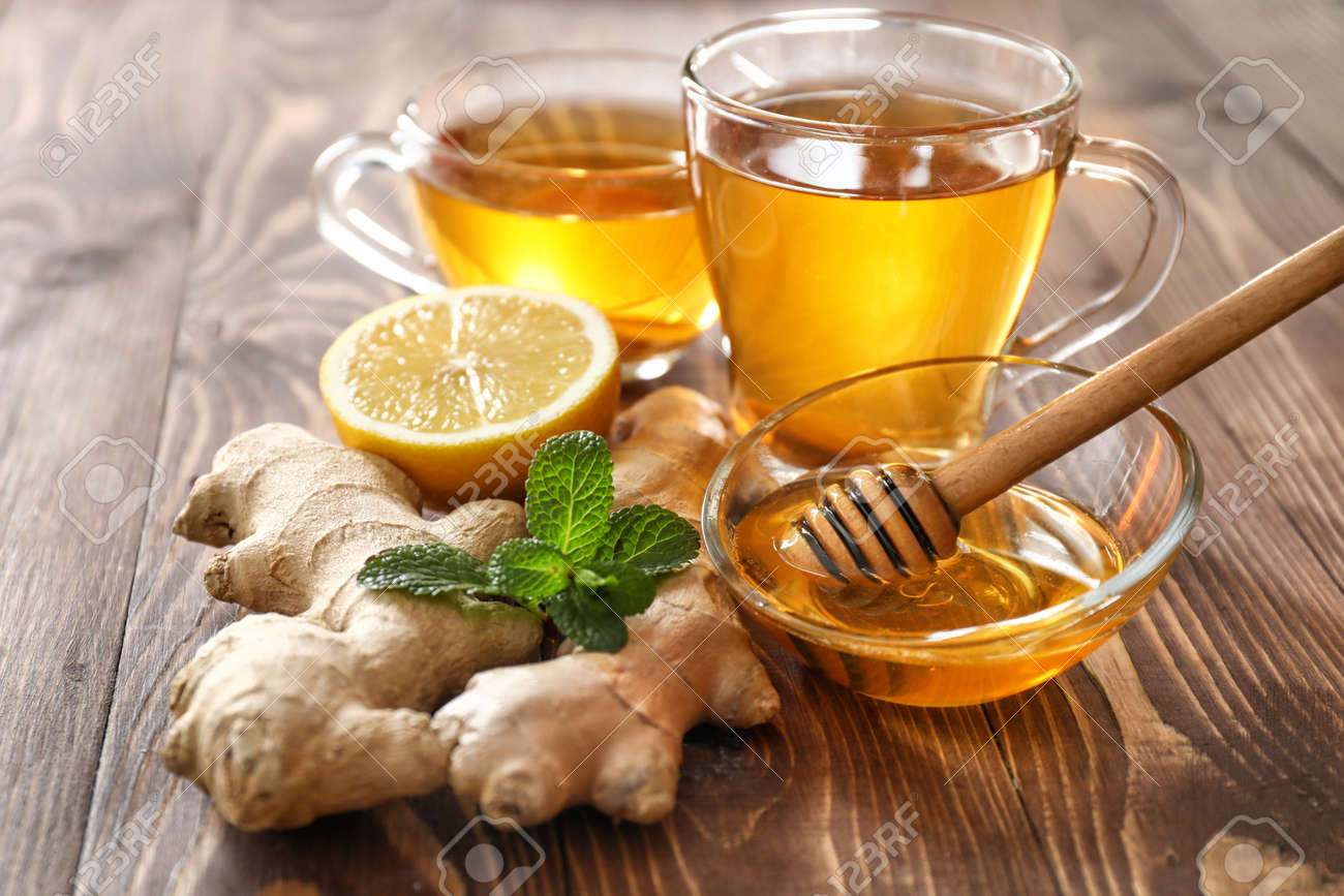 Cups of healthy drink with lemon, ginger and honey on wooden table - 165918667
