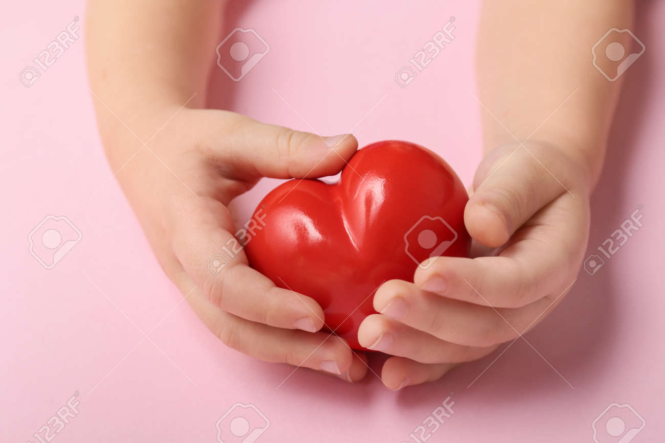 Child's hands with red heart on color background. Cardiology concept - 166064690