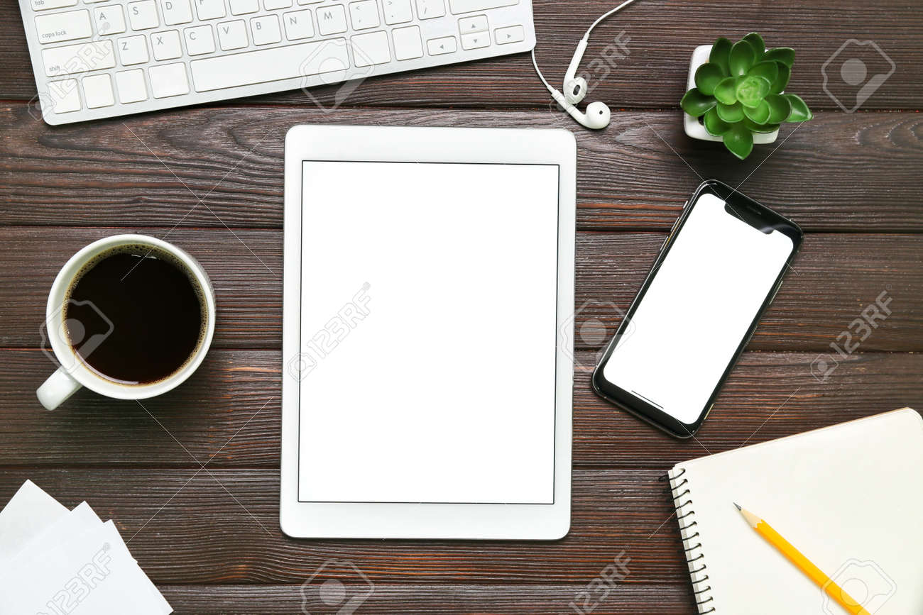 Mobile phone, PC keyboard, tablet computer, cup of coffee and stationery on wooden background - 166276737