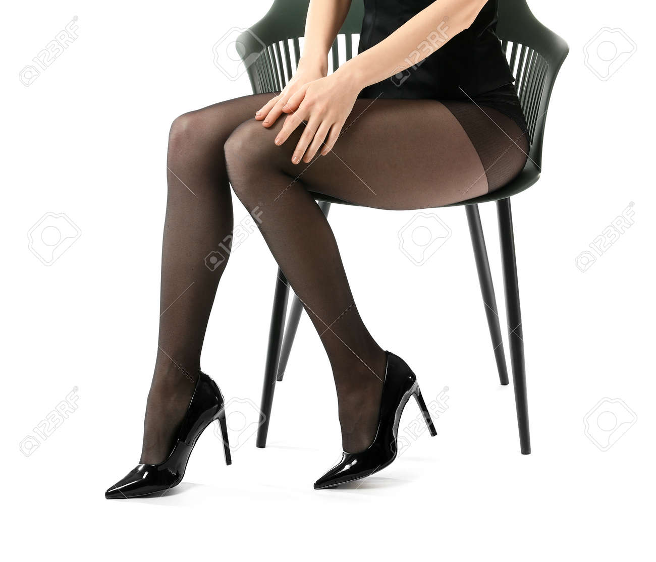 Beautiful young woman in tights sitting on chair against white background - 166666696