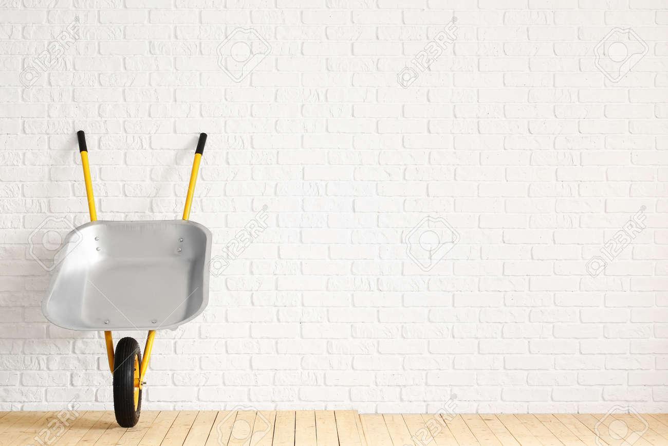 Empty wheelbarrow near white brick wall - 166685563