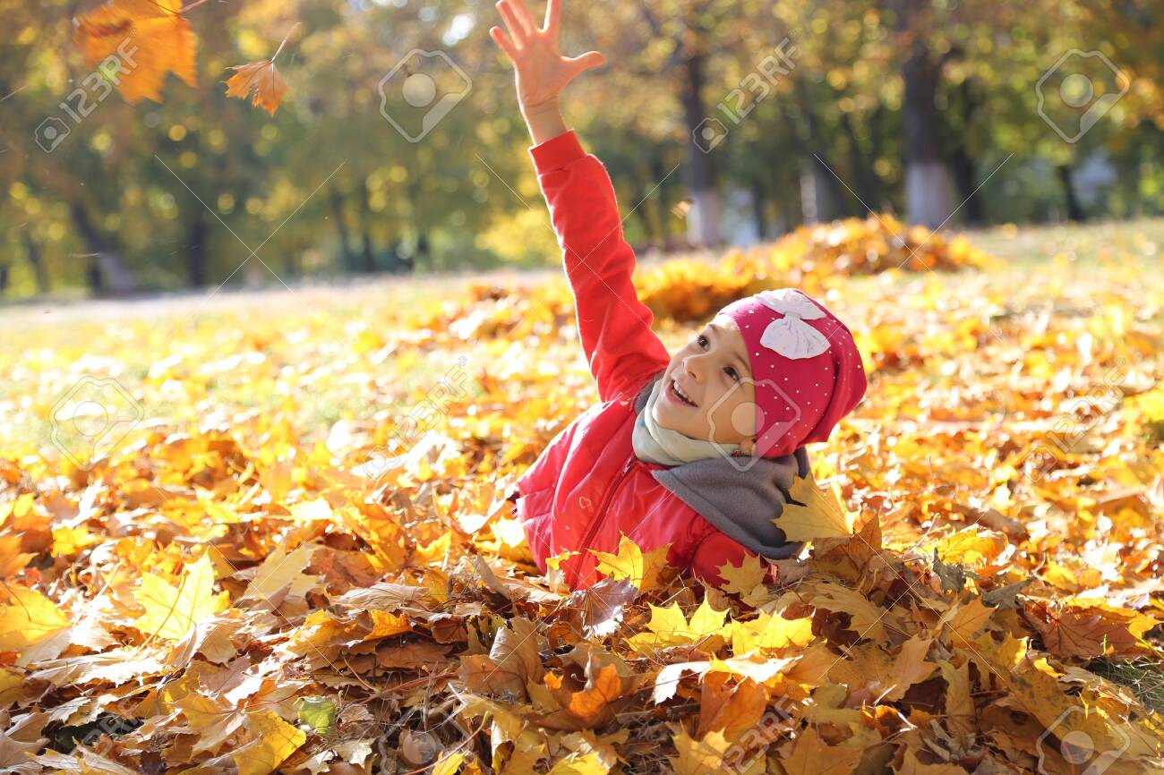 happy little baby girl playing in autumn in yellow leaves - 121430571