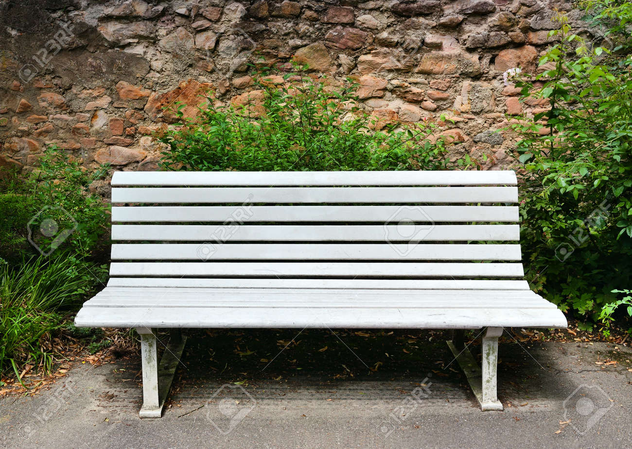 wooden bench near a stone wall stock photo picture and royalty  - stock photo  wooden bench near a stone wall