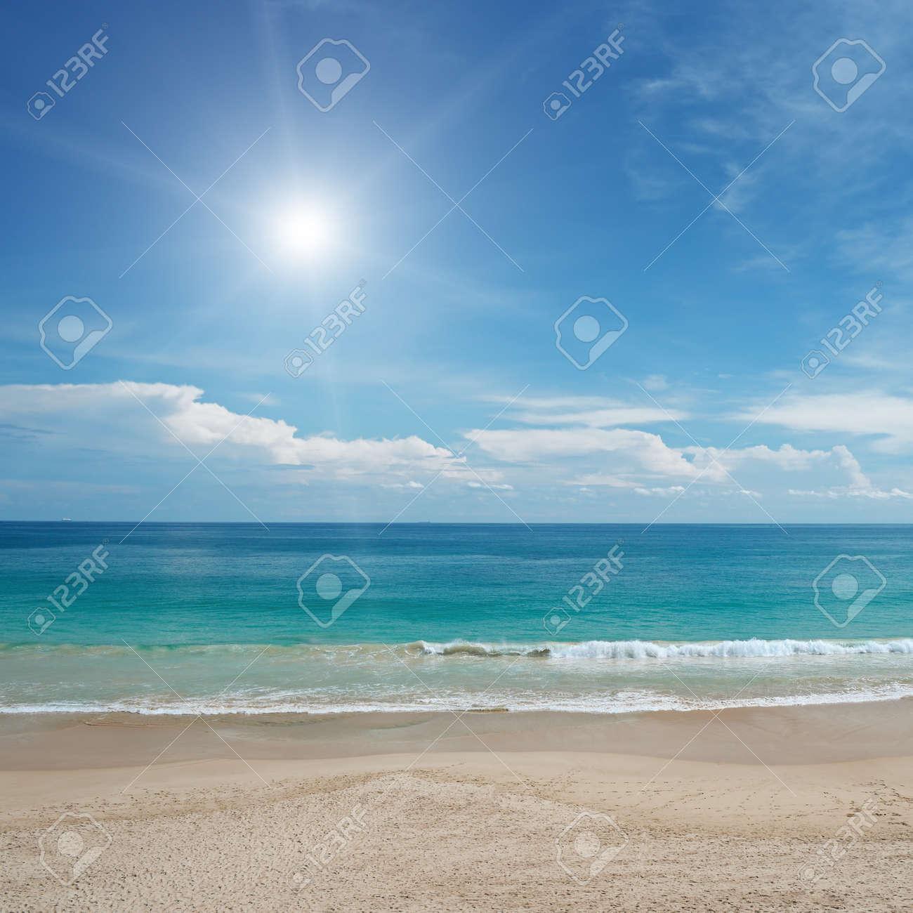 Sandy beach and sun in blue sky - 34106915