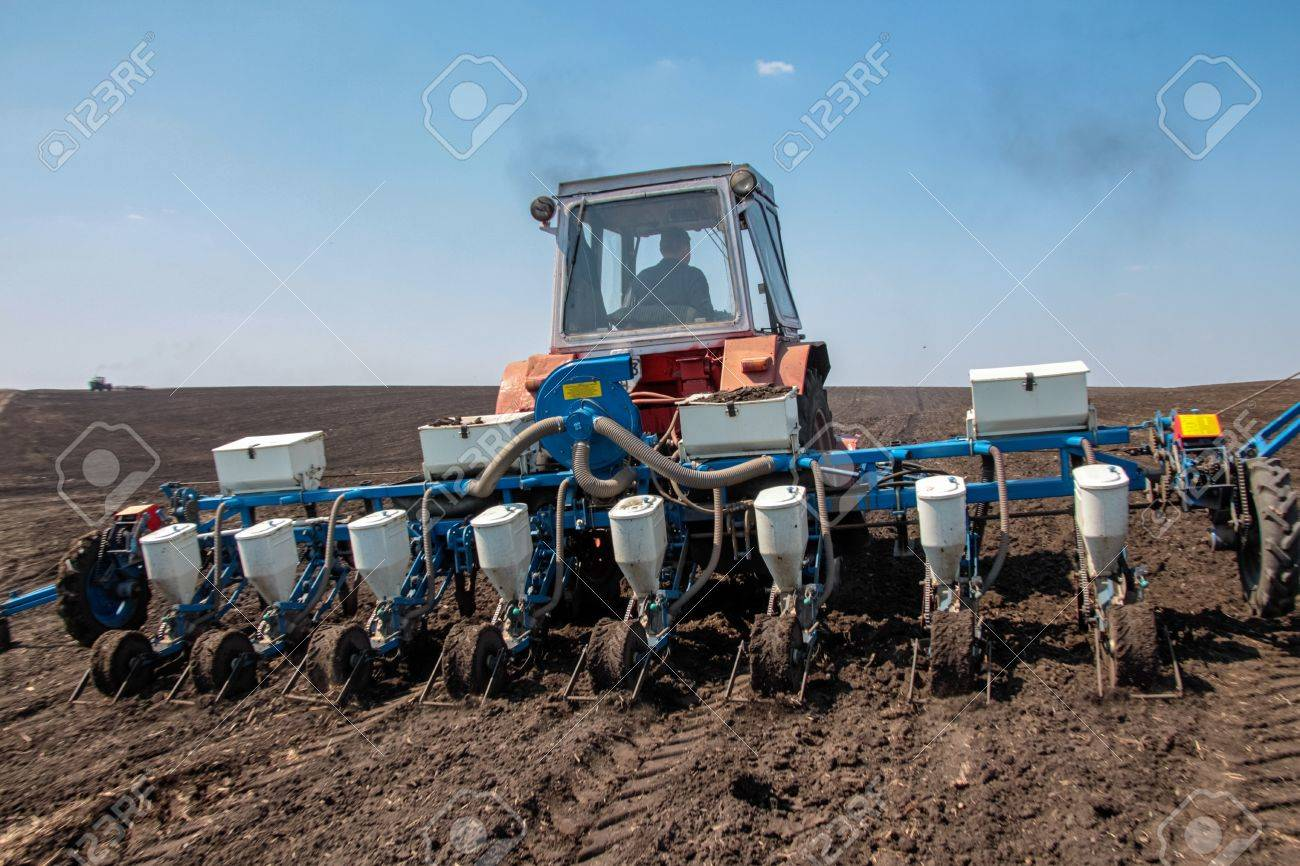 Tractor with sower on the field in bright sunny spring day Stock Photo - 20198565