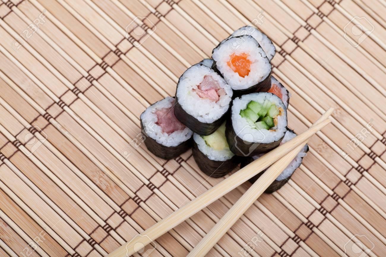 Closeup Sushi And Chopsticks On Bamboo Mat Top View