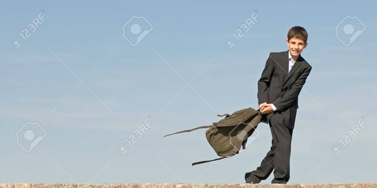 a happy pre-teen is coming back from school holding his schoolbag in his hands Stock Photo - 5578944