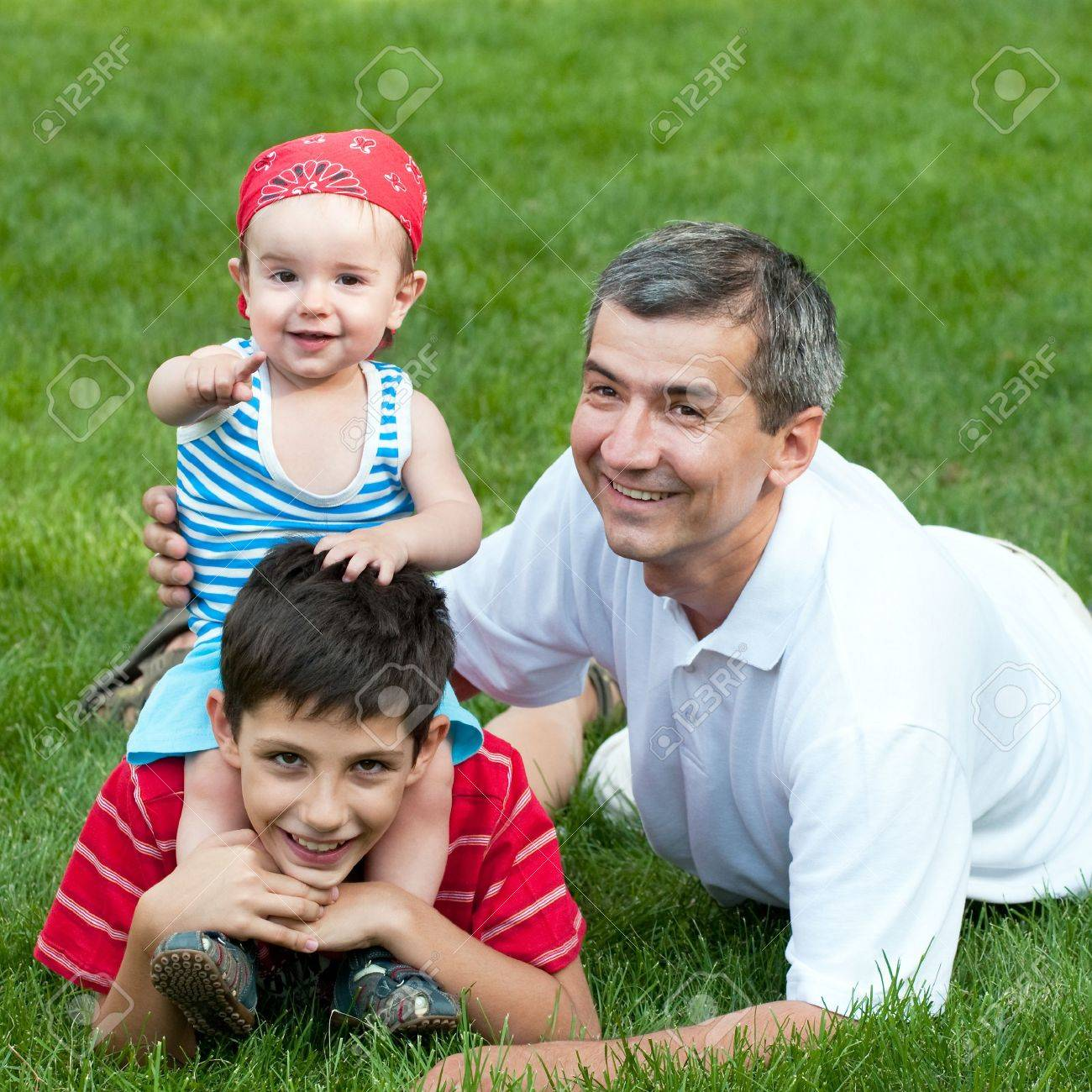 A father and his sons are playing on the grass in the park