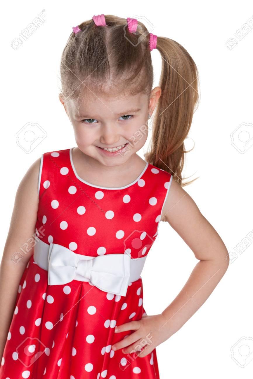 Una Niña Sonriente Con Un Vestido Rojo De Lunares Está De Pie En El Blanco