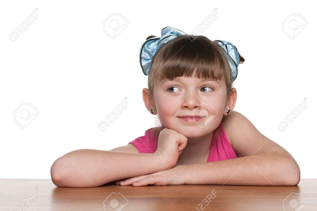 Une petite fille curieuse assis à un bureau de l école sur le fond