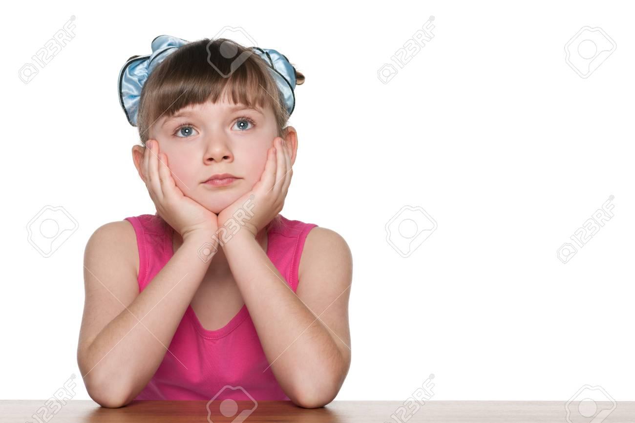 Une petite fille pensive assis à un bureau de l école contre le