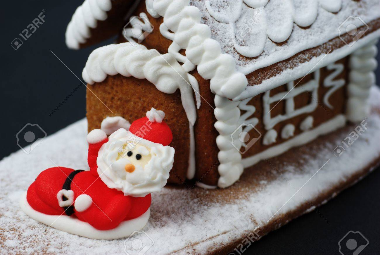 Santa Claus in front of gingerbread house. Stock Photo - 10726099