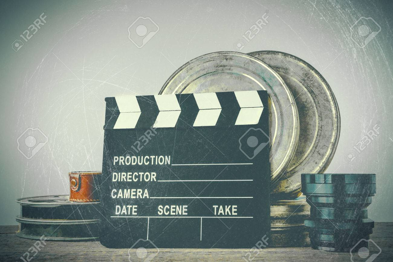 Clapperboard, tin boxes with film and lens stand on a wooden