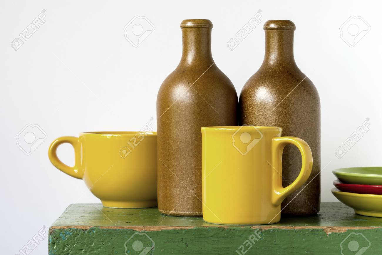 Colored Ceramic Bottles Cups And Saucers Stand On A Green Wooden