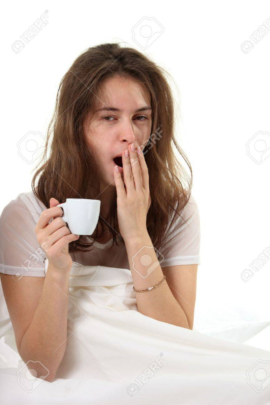 Young woman sitt in a bed with a cup of coffee and yawn Stock Photo - 8406443
