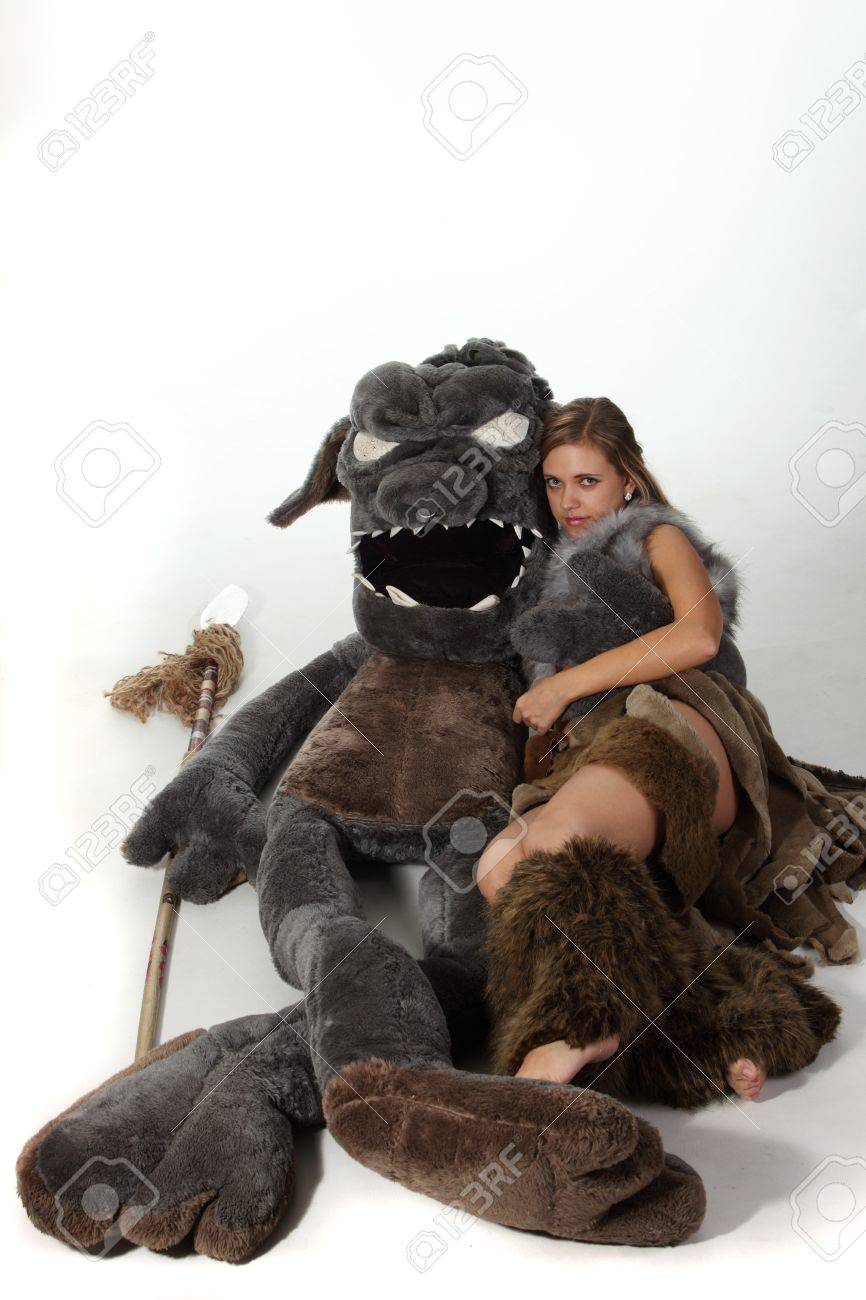 Young attractive girl in costume of savage woman lie with a monster Stock Photo - 9133532