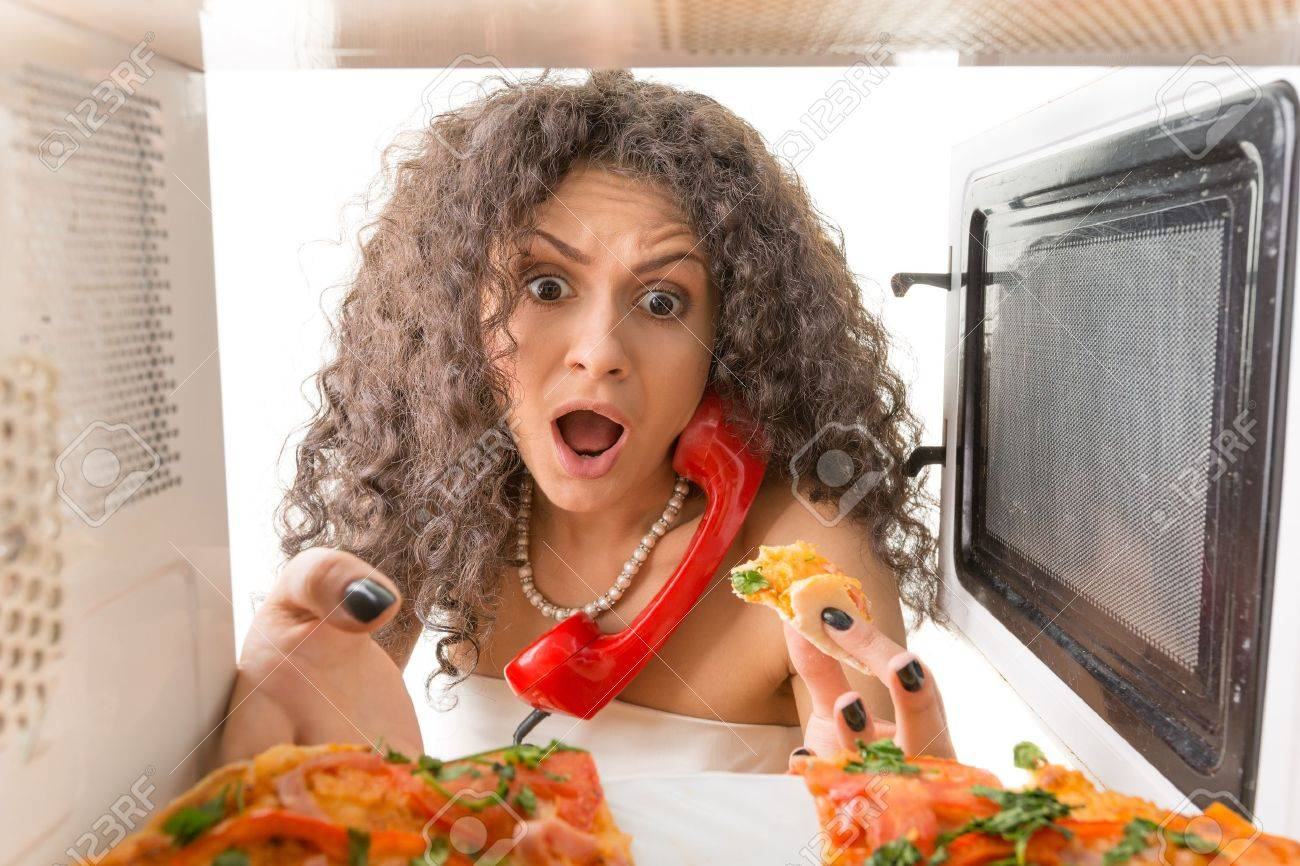 Girl preparing a pizza and talking on the phone Stock Photo - 19667586