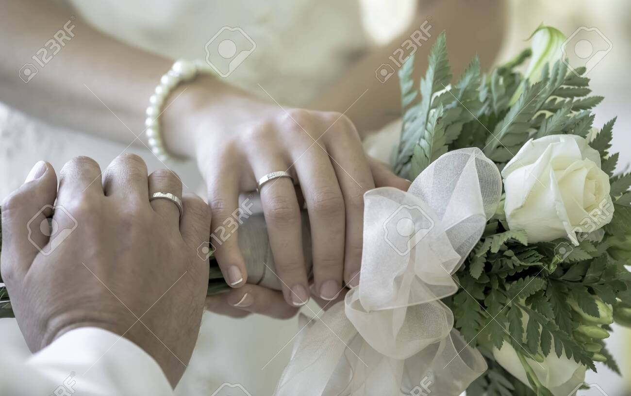Hands of the bride and groom in white wedding dress with wedding..