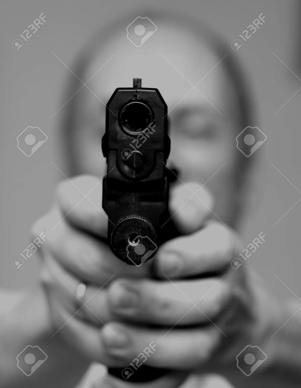 Man with a gun.Old man pointing a gun towards the camera. Stock Photo - 9617364