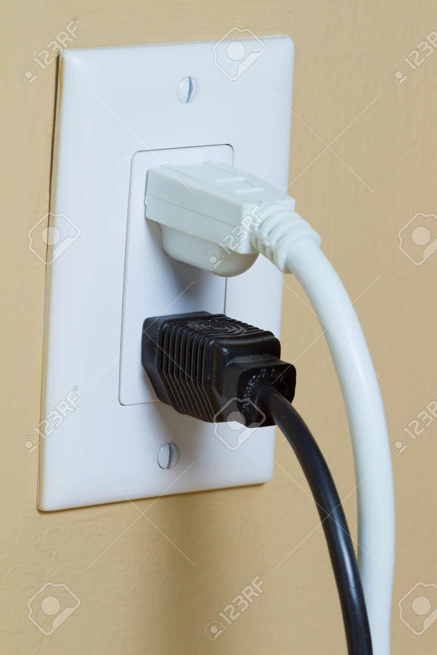 zwei elektrische schwarze und weiße kabel in steckdose an der wand