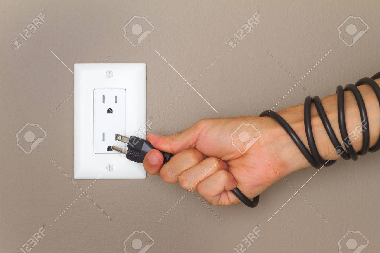 Electric Cable On The Hand And Electrical Outlet On The Wall ...
